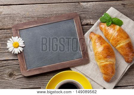Blackboard, croissants, flowers and coffee cup. Top view with copy space