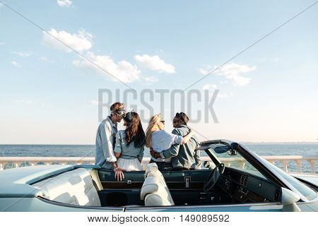 Back view of two happy young couples standing and hugging near the car