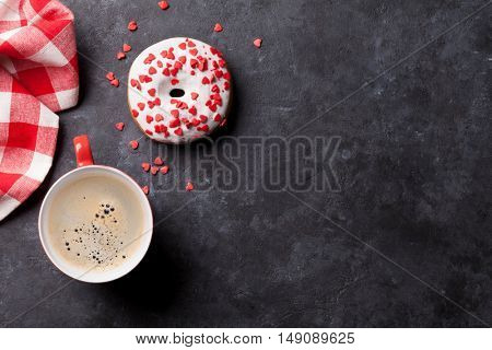 Donut and coffee on stone table. Top view with copy space