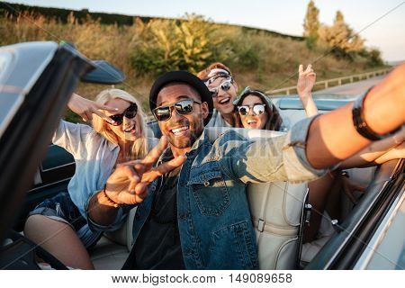 Multiethnic group of cheerful young people taking selfie in the car