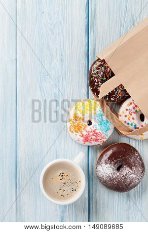 Colorful donuts in paper bag and coffee cup on wooden table. Top view with copy space