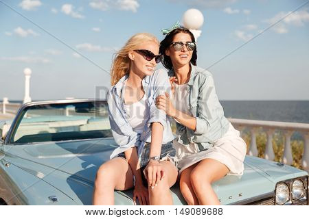 Two happy young woman sitting together on cabriolet in summer