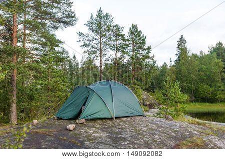 Big green tourist tent in the rocks of small island in Ladoga lake, Karelia, Russia.