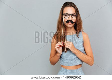 Funny cute young woman with glasses and moustache props over grey background