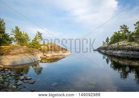Beautiful mirror water and stone shores of Karelia islands. Ladoga lake, Russia.