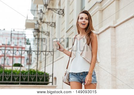 Smiling cheerful young girl holding take away cup and walking outdoors