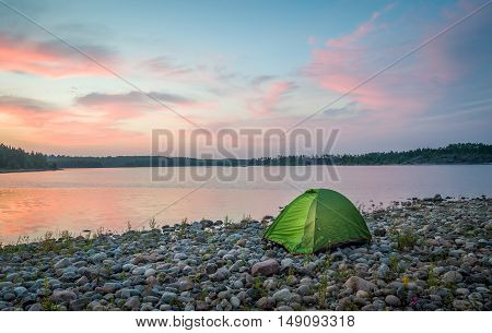 Beautiful sunset view on the calm lake and small tourist tent near the water. Ladoga lake islands, Karelia, Russia.