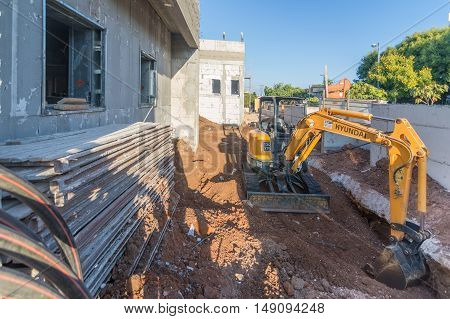 Bulldozer And Brick And Concrete House Under Construction