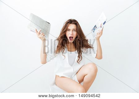 Irritated young brunette woman in casual wear holding newspapers and looking at camera isolated on a white background