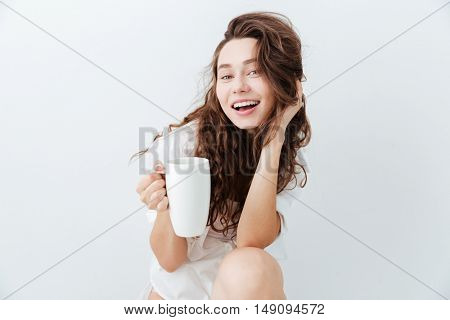 Charming lovely young woman with long hair holding cup and smiling isolated over white background