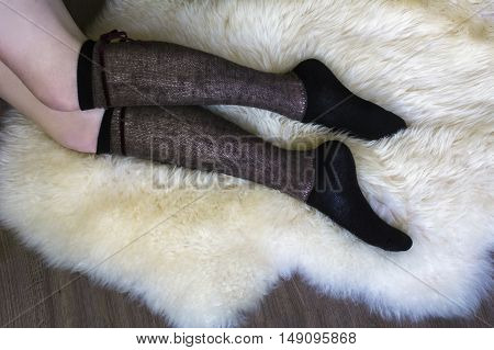 Woman legs in brown knee socks on the white fur