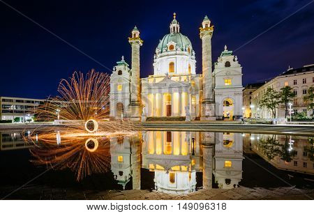 Magical evening view of the St. Charles Church (Karlskirche) and fire show. Historical scene, famous tourist attraction. Location place Karlsplatz in Vienna. Austria, Europe. Beauty world.