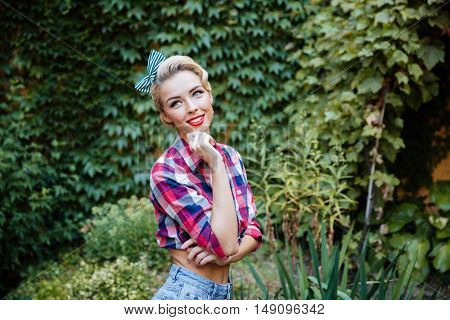 Smiling pretty pin-up girl standing and dreaming in the garden