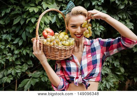 Happy playful pin-up girl with basket of fruits covered her eye with grape in the garden