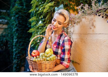 Portrait of smiling cute pinup girl sitting and holding basket of fresh fruits