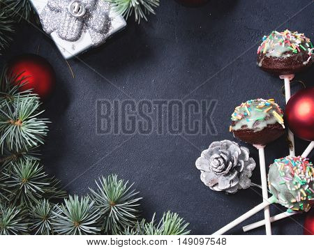 Blue spruce branches with christmas baubles and cake pops with colored sprinkles on green frosting on dark black concrete effect background. Copy space