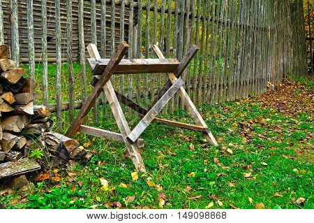 Sawbuck - wooden device for cutting firewood and the stack of wooden logs near the wooden fence