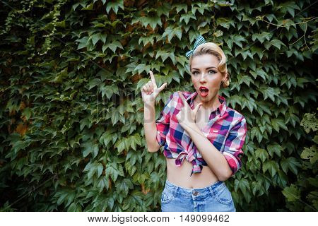 Surprised charming young woman standing and pointing away in the garden