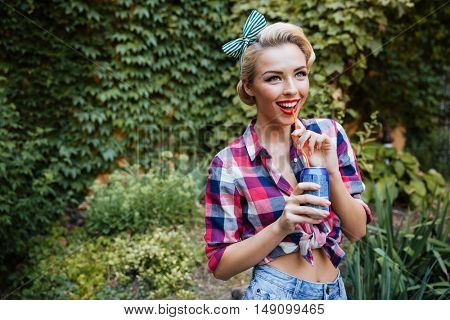 Cheerful lovely pinup girl walking in the park and drinking soda