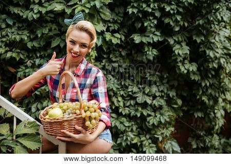 Cheerful cute pinup girl with basket of fruits showing thumbs up outdoors