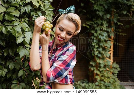 Cheerful cute pin-up girl smiling and eating grape outdoors