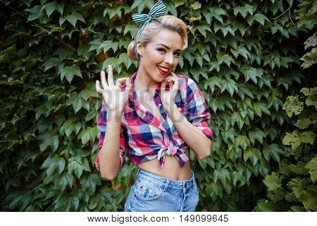 Smiling charming young woman standing and showing ok gesture in the park