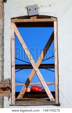 Looking up to the blue sky through vintage window without glass. Wall is the rest of a house. Window is secured with two crossbreded timbers.