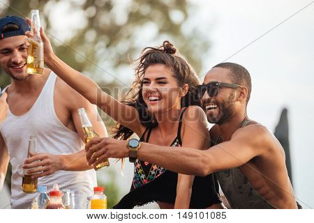 Cheerful young friends drinking beer and having fun outdoors