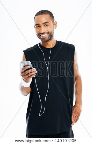 Portrait of smiling young african male athlete listening to music with earphones and cell phone over white background