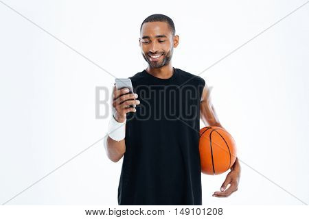 Smiling young basketball player standing and listening to music from smartphone isolated on a white background