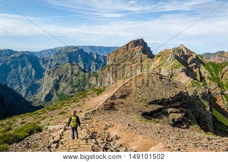 Tourist woman walking on the mountains of Madeira island. Pico Arieiro to Pico Ruivo hiking path, Madeira island, Portugal.