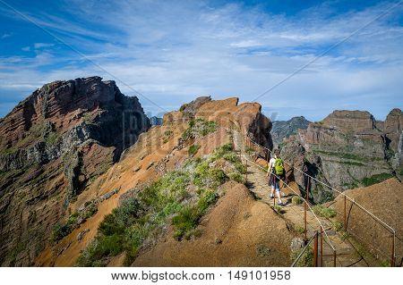 Woman hiker with green backpack doing her hike of Pico Arieiro to Pico Ruivo hiking route. Madeira island popular hike, Portugal.
