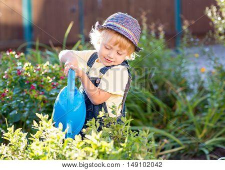 Boy watering flowers as gardener