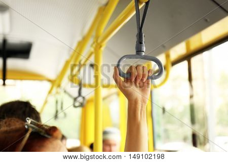 Hand holding handle on the public transport
