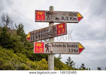 Wooden road sigh in the mountains of Madeira island with directions to popular hiking paths.