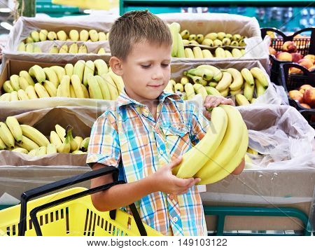 The boy buys bananas in the store