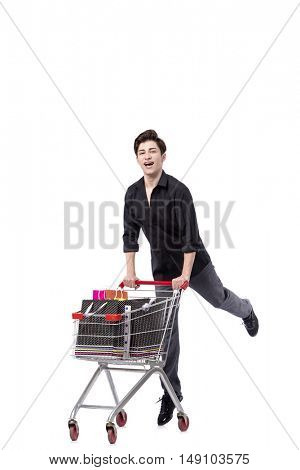 Young man with shopping cart and bags isolated on white