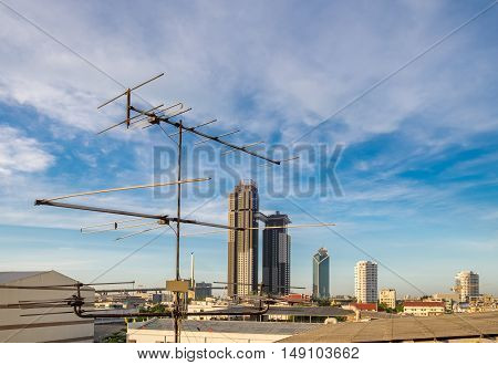 Televisions antennas on rooftop with cloudy sky background.