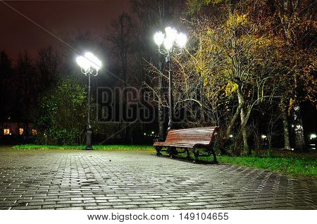 Night autumn landscape of night autumn park. Autumn rainy night with lonely bench under yellowed autumn trees-night landscape. Night city view of autumn city park. Colorful autumn night landscape