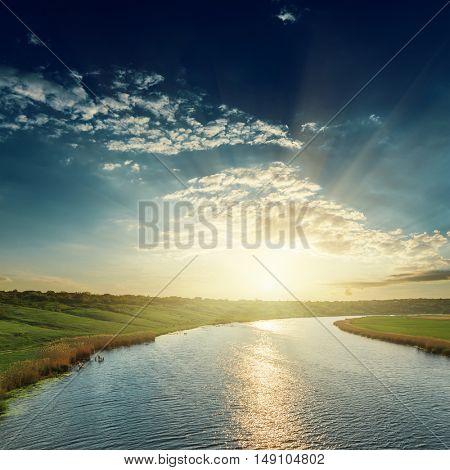 sunset in dark sky over river