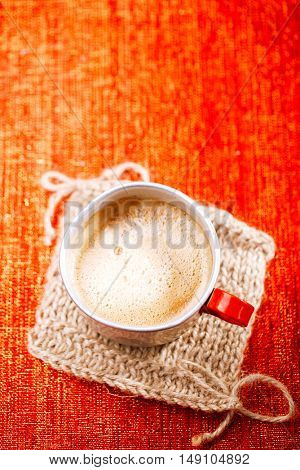 coffee in unusual vintage tin mug with red handle on red glitter backdrop