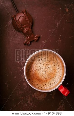 coffee in unusual vintage tin mug with red handle on old metal backdrop with chocolate candy