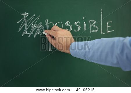 Businessman putting a cross over word impossible on blackboard