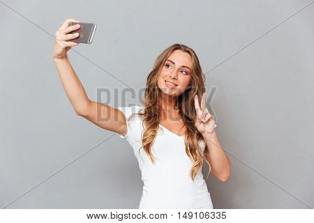 Smiling young woman in hat making selfie photo and showing peace gesture over gray background