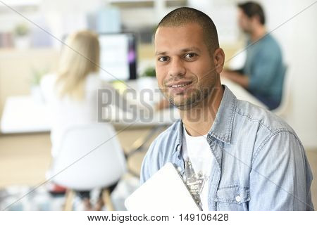 Portrait of office-worker holding tablet