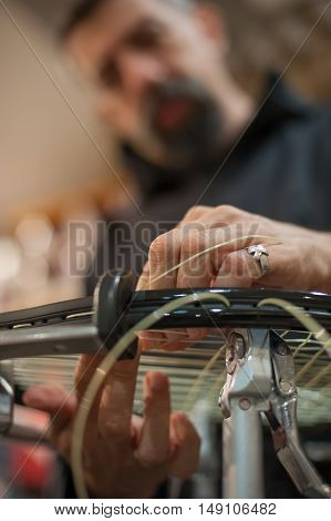 Close Up Of Tennis Stringer Hands Doing Racket Stringing