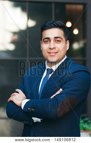 Prosperous entrepreneur with folded arms. Succeessful businessman portrait., modern glass building background. Business, success, progress concept