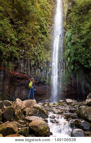 Woman tourist is standing next to the big waterfall at levada 25 fountains in Rabacal, Madeira island, Portugal. Vertical photo.
