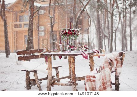 Table Made Of Pine In Snowbound Forest In Winter With Red Wedding Table Setting. Winter Wedding Deco