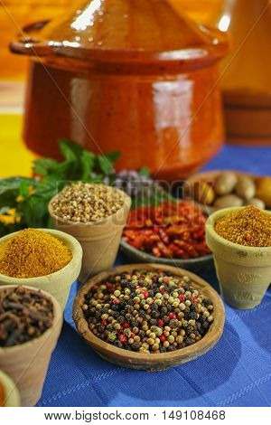 Collection of different spices in old clay bowls in colorful oriental style